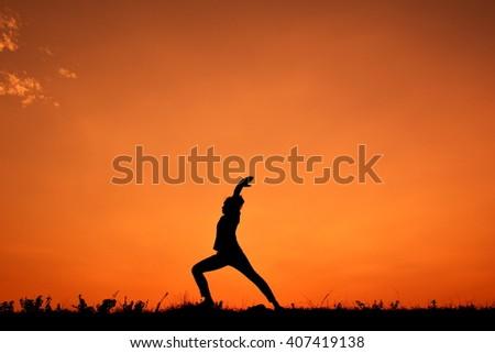 Silhouette women yoga at sky sunset - stock photo