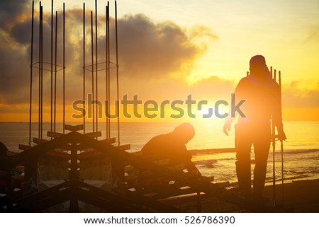 silhouette worker working with sun flare effect on sunrise time on side near the sea.