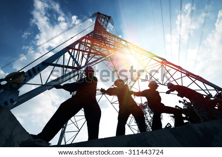 silhouette workers on background of construction - stock photo