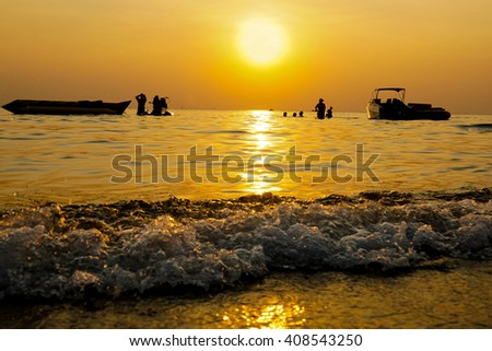 Silhouette yacht , boat and jet ski on water surface in yellow sunset beach time - stock photo