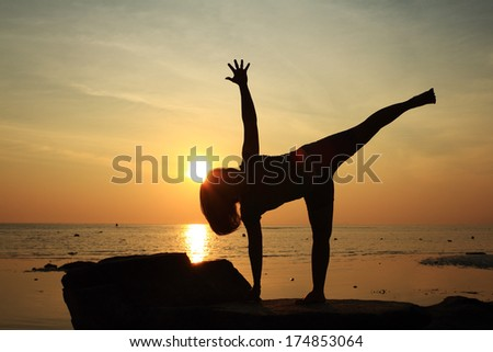 Silhouette yoga girl by the beach at sunrise doing Half Moon  Pose - stock photo