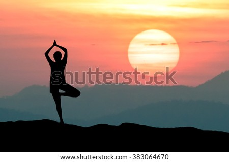 Silhouette Yoga practitioner during the twilight Omega or Inferior-Mirage sunset meditation