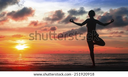 Silhouette yoga woman on ocean beach at magic blood-crimson sunset. - stock photo