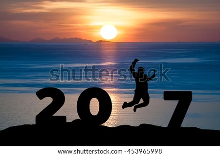 Silhouette young business man jumping on the sea and 2017 years while celebrating new year