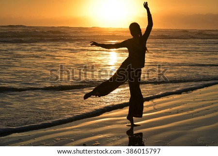 Silhouette young girl dancing with hands up on the beach at the sunset