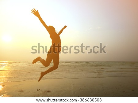 Silhouette  young girl  jumping with hands up on the beach at the sunset,motion blur