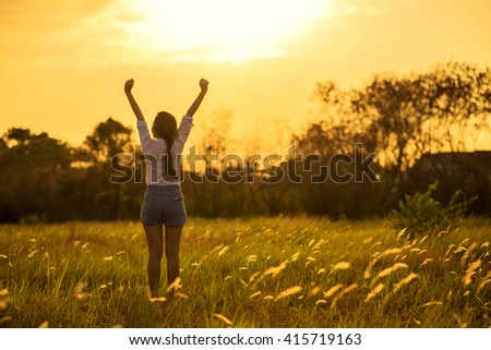 Silhouette Young happy woman in meadow  field on sunset.