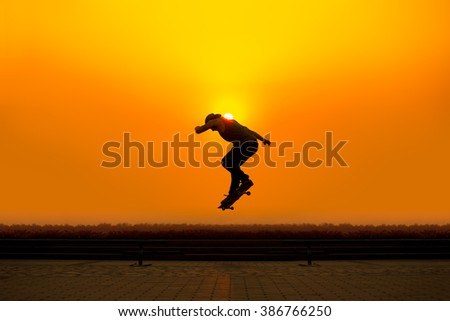 silhouette young man playing skateboard with height jump in evening time with sunset yellow orange background