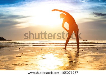 Silhouette young woman, exercise on the beach at sunset