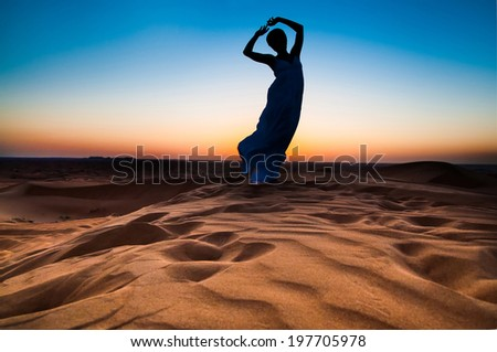 silhouette young woman in sandy desert at sunset - stock photo