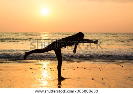 Silhouette young woman jumping and dancing in the sunset on the beach. vacation vitality healthy living concept
