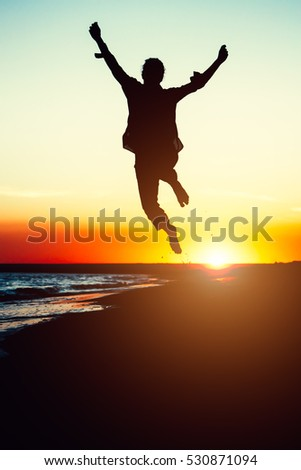 Silhouette young woman jumping with hands up on the beach at the sunset. Travel photo summertime