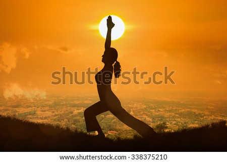 Silhouette young woman practicing yoga at orange sunset background