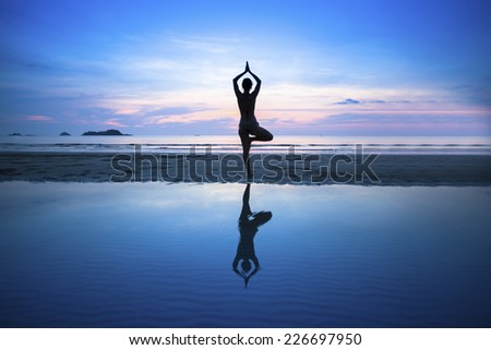 Silhouette young woman practicing yoga on beach at surrealistic sunset. - stock photo