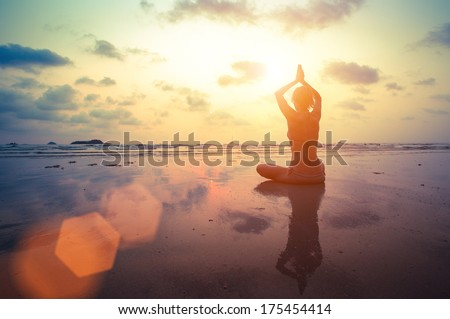 Silhouette young woman practicing yoga on the beach at surrealistic sunset. - stock photo