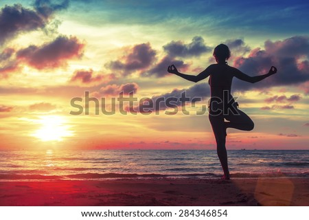 Silhouette young woman practicing yoga on the beach at surrealistic sunset. Healthy lifestyle choices. - stock photo
