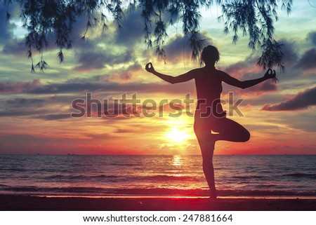 Silhouette young woman practicing yoga on the sea beach at blood-surrealistic sunset.