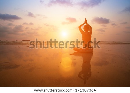 Silhouette young woman practicing yoga on the sea beach at sunset. - stock photo