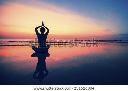 Silhouette young woman practicing yoga on the sea beach at surrealistic sunset.