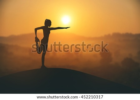 Silhouette young woman practicing yoga on themuontain at sunset.