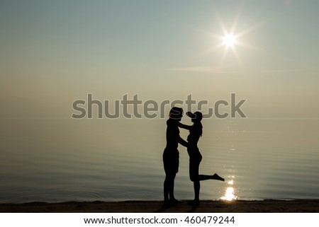 Silhouette. Young woman together with men. They enjoy the sunset on the beach and they feel the harmony and love. Serene and warm, gentle water. Touch to each other.  In front of view opens infinity.