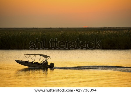 Silhouetted boat on a river safari on the Chobe River, Botswana, Africa - stock photo