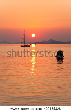 Silhouetted boat with sunset over Cavtat near Dubrovnik Croatia - stock photo