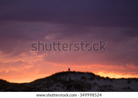 silhouetted boy on sand dune on French coast at sunset - stock photo
