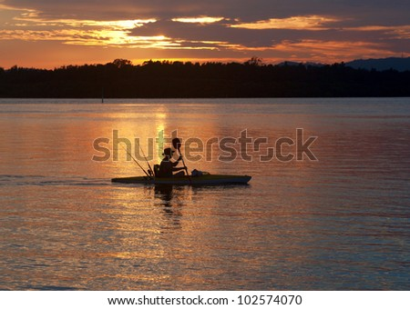Silhouetted canoeist at sunrise