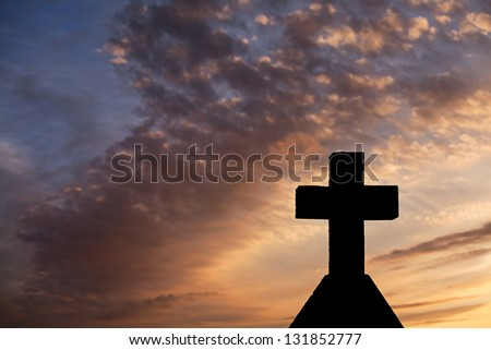 Silhouetted christian cross in a graveyard at sunset