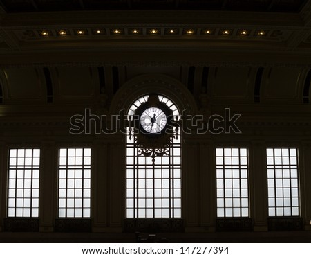 Silhouetted clock and windows of historic train station - stock photo