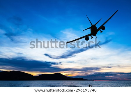 Silhouetted commercial airplane flying above the sea at sunset - stock photo
