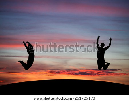 silhouetted couple jumping in sunset sky  - stock photo