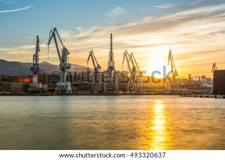 silhouetted cranes at shipyard,