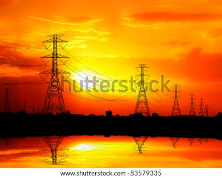 silhouetted electric pylon with power line at sunset - stock photo