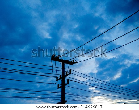 Silhouetted Electricity post with against blue sky at dark.