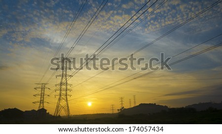 Silhouetted electricity transmition pylons against sunrise.