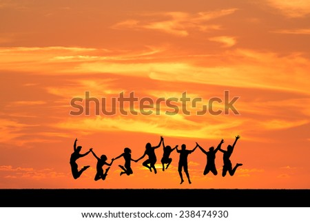 silhouetted friends jumping in sunset  - stock photo