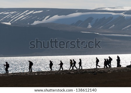 Silhouetted group of hikers along an inlet in Barentsoya, Svalbard, Norway within the arctic circle.