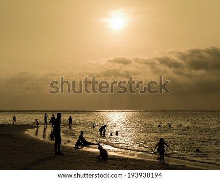 silhouetted group of people on the beach and in the sea under sunbeam in the evening with gray tone - stock photo