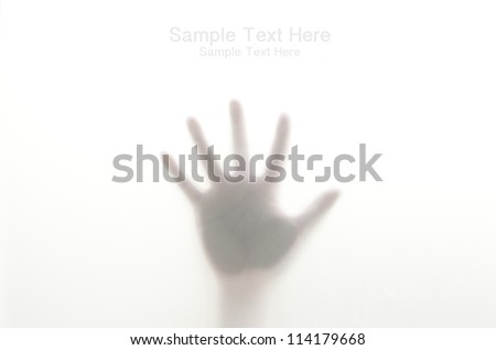 Silhouetted hand on frosted glass - stock photo