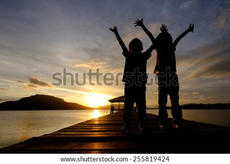 Silhouetted Happy and joyous kids (boy and girl) in excitement spreading their arms while looking to the sky during sunrise  - stock photo