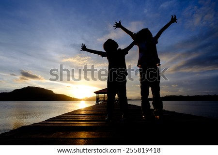 Silhouetted Happy kids (boy and girl) spreading their arms while looking to the sky during sunset with a blue sky - stock photo