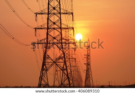 Silhouetted high voltage electric pylon in sun set background