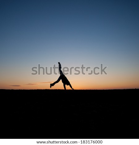 silhouetted man doing a cartwheel in sunset sky  - stock photo
