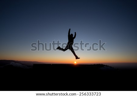 silhouetted man jumping on mountain in sunset