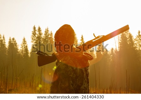 Silhouetted of a hunter with shotgun at beautiful sunset - stock photo