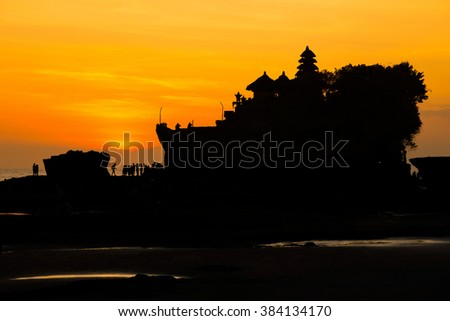 Silhouetted of Tanah Lot and sea waves in twilight, Bali, Indonesia. - stock photo