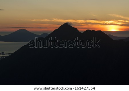 Silhouetted peak of Mount Verstovia with volcano Mount Edgecumbe in background near Sitka, Alaska during magnificent summer sunset - stock photo