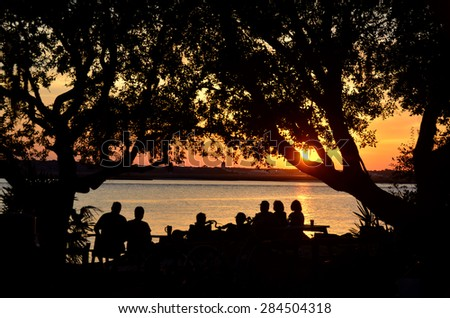 Silhouetted People Looking at the majestic sunset from the river's edge at St, Augustine, Florida. Soft focus - stock photo